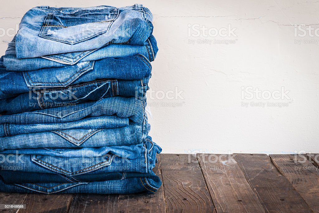 stack of various shades of blue jeans on old wood stock photo