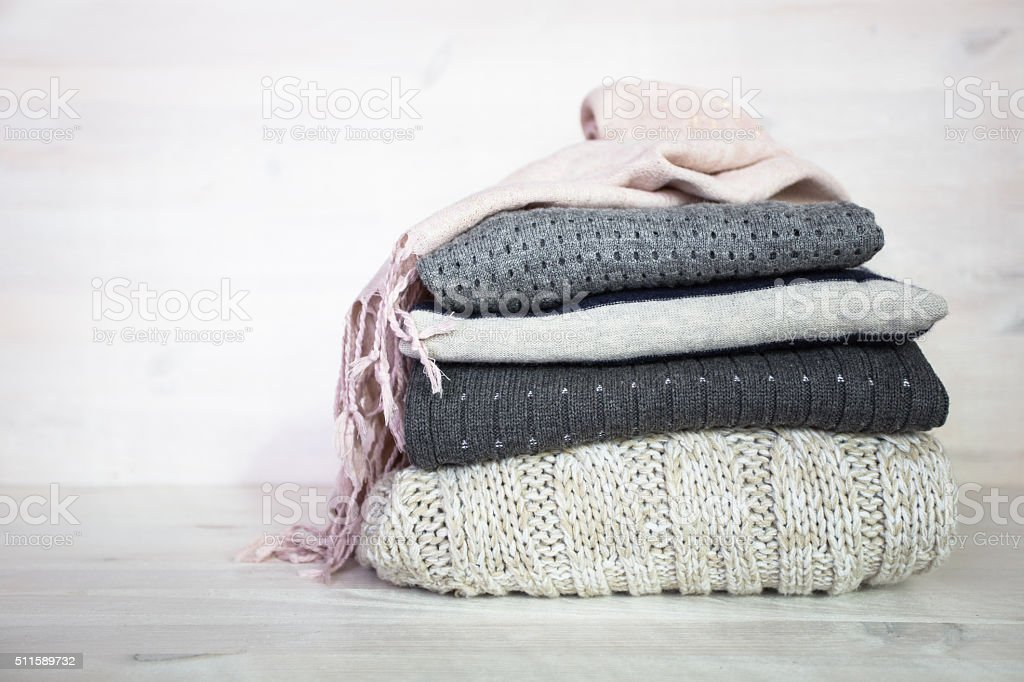 stack of various woolen sweaters on a white wooden background stock photo