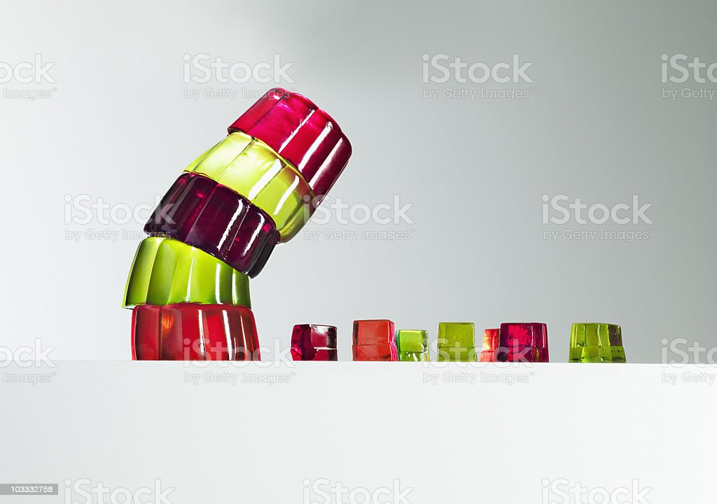 Stack of vibrant gelatin dessert leaning over small gelatin dessert cubes stock photo