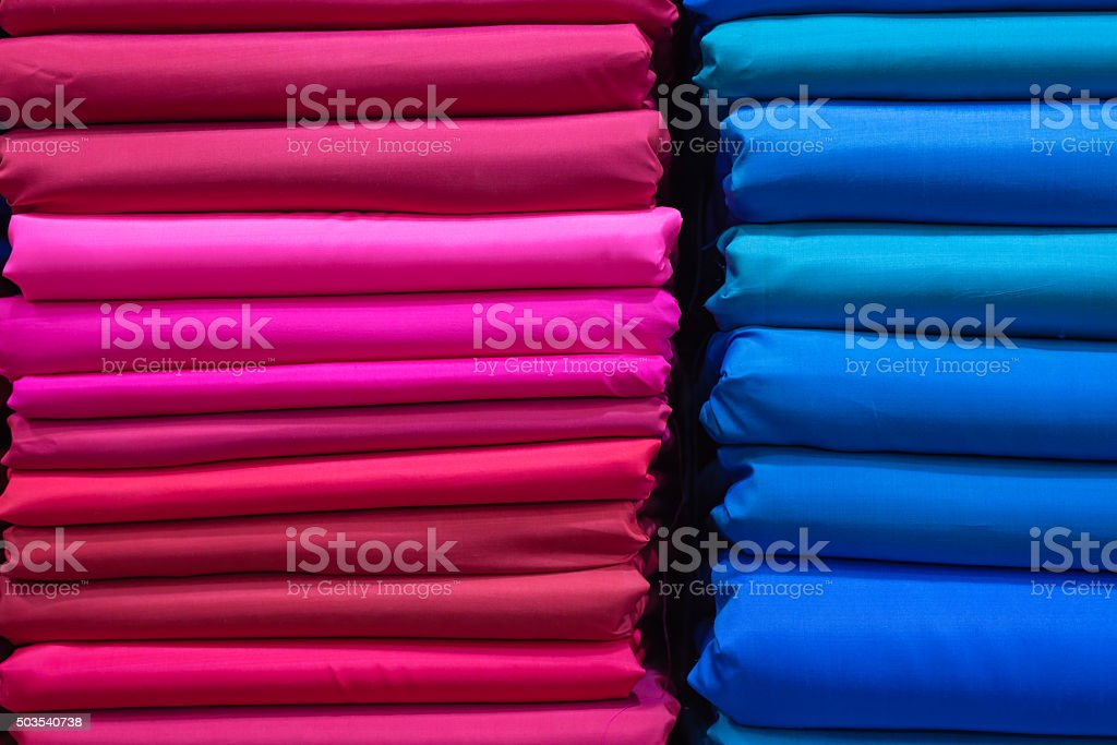 stack of vibrant pink and blue silk fabric stock photo