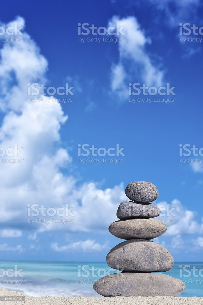 Stack of volcanic pebbles on a sandy beach stock photo