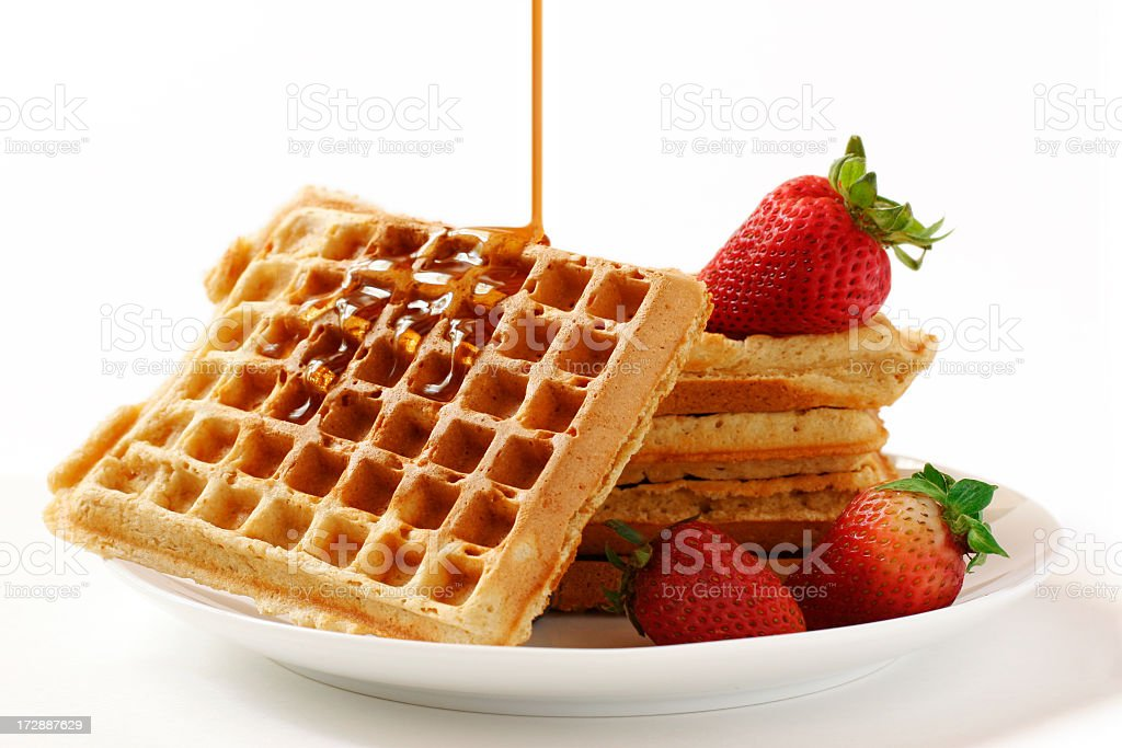 Stack of waffles and strawberries dripped with syrup royalty-free stock photo