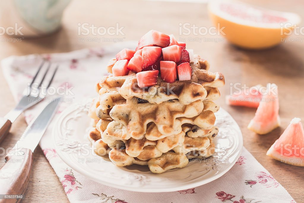 Stack of waffles, grapefruit and strawberries for breakfast stock photo