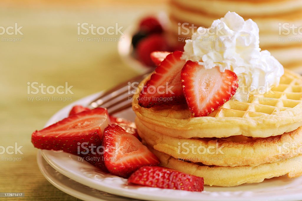 A stack of waffles with strawberries stock photo