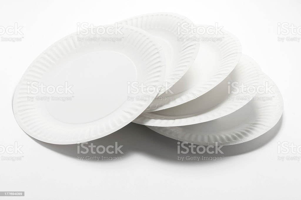 Stack of white paper plates on white surface stock photo
