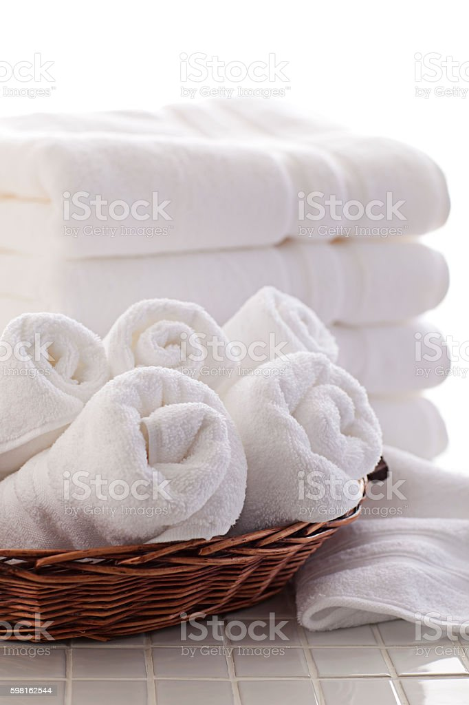 stack of white towels and basket of rolled towels stock photo