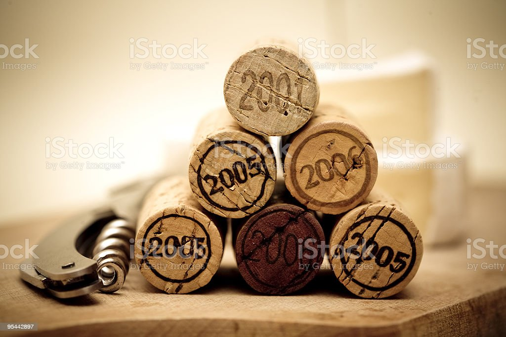 Stack of wine corks with dates on them next to a wine opener royalty-free stock photo