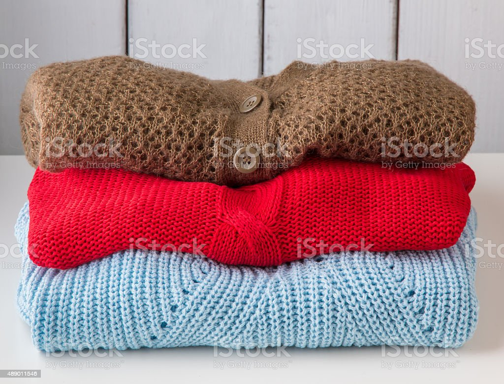 Stack of women's sweaters and cardigans. stock photo