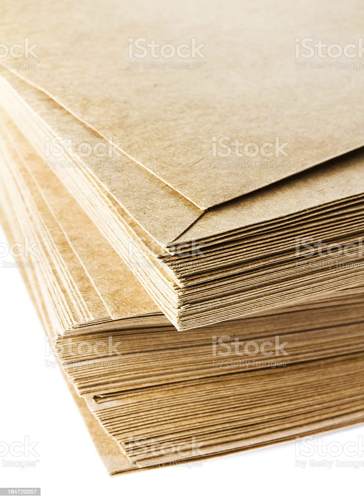 Stack of yellow recycled paper envelopes isolated on white backg royalty-free stock photo