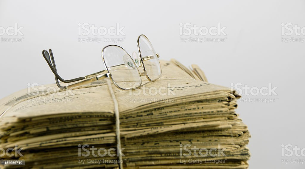 Stack of Yellowed Newspapers and Glasses royalty-free stock photo