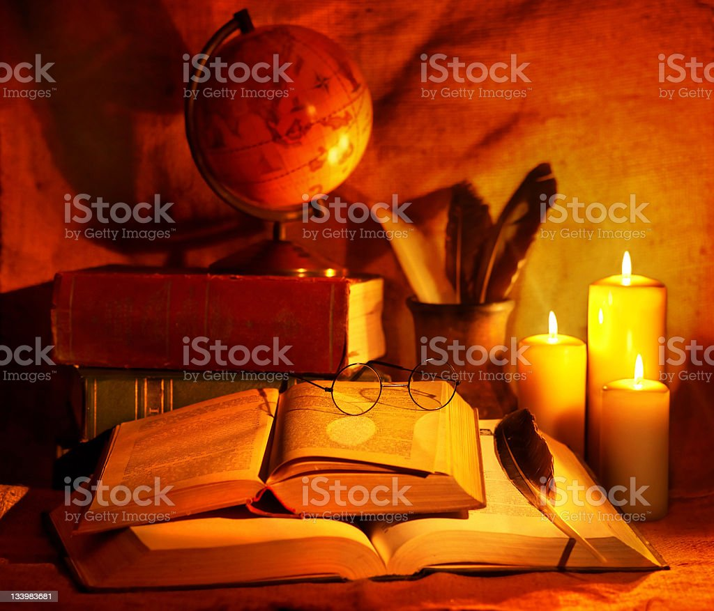 Stack old book and candle. stock photo