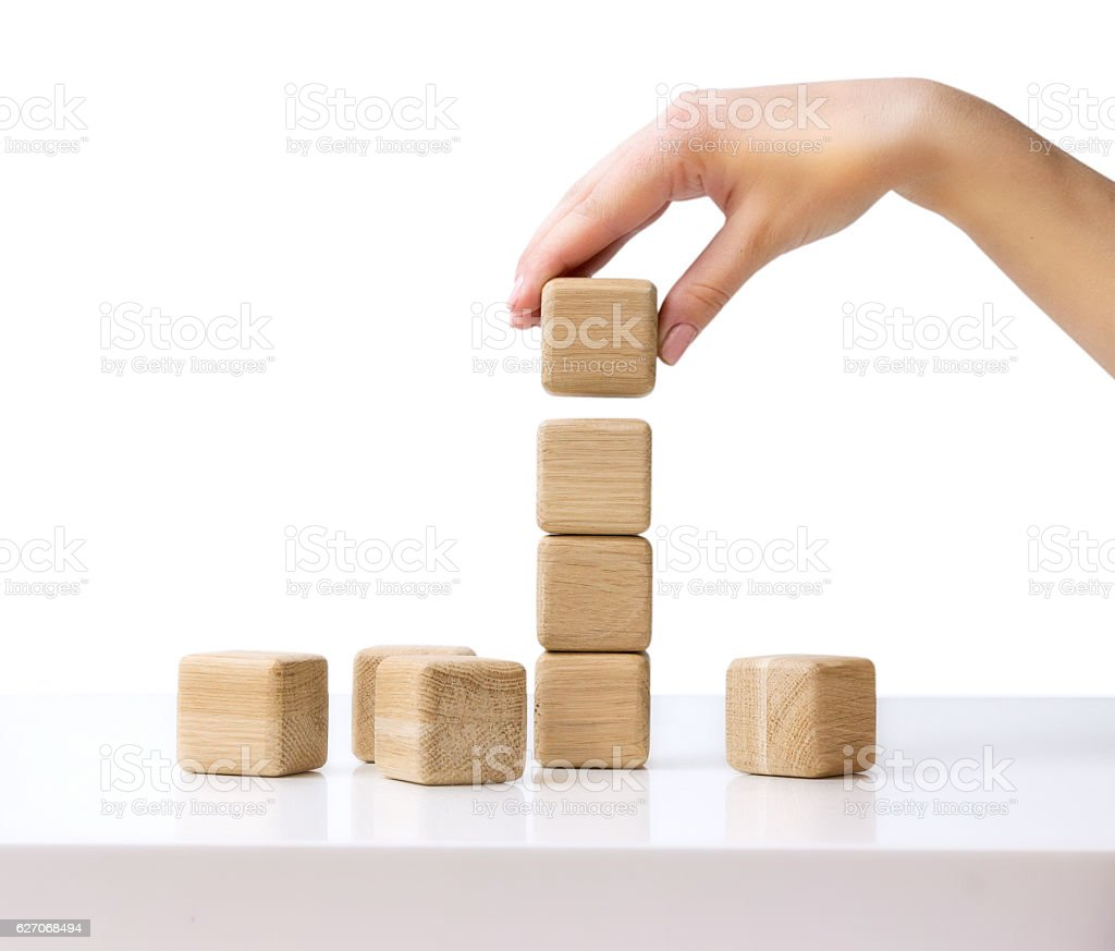 Stack wooden cubes.Hand establishes block tower isolated. stock photo