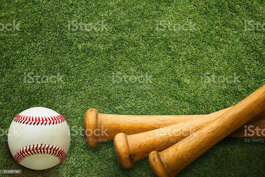 Stacked Baseball Bats and Ball on Grass  Field stock photo