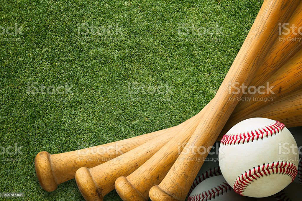 Stacked Baseball Bats and Ball on Grass Field stock photo