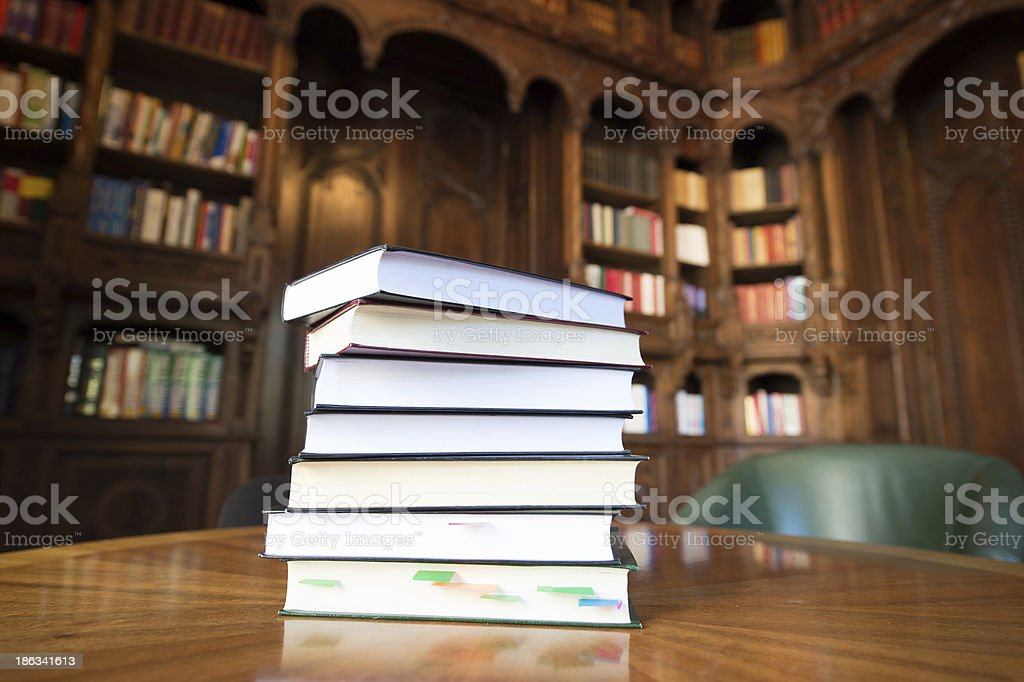 Stacked books with library in the background royalty-free stock photo