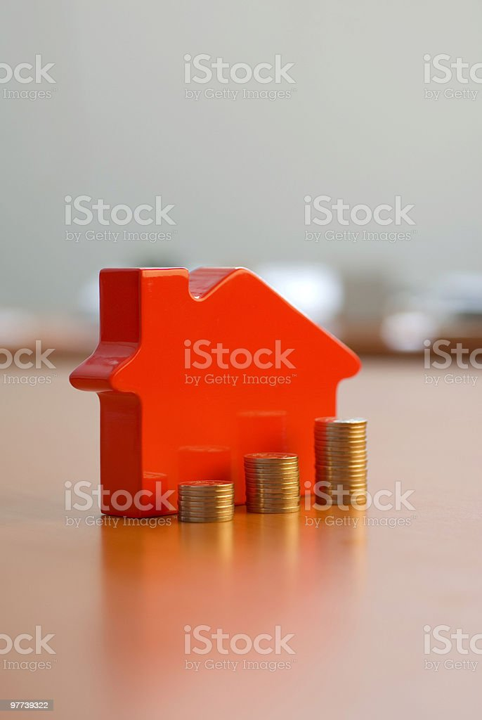 Stacked coins in front of a toy house stock photo