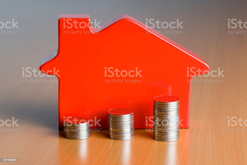 stacked coins in front of toy house stock photo