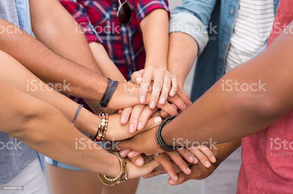 Stacked hands of friends stock photo
