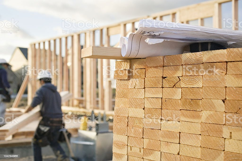 Stacked Lumber and Blueprints at a Construction Site stock photo
