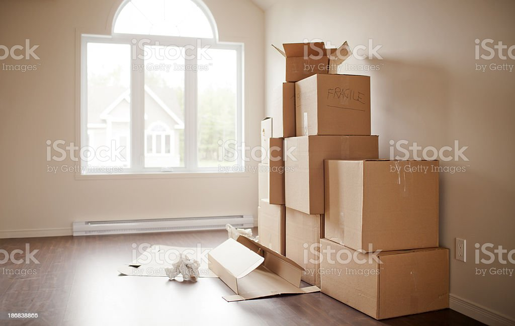 Stacked moving boxes along house walls royalty-free stock photo