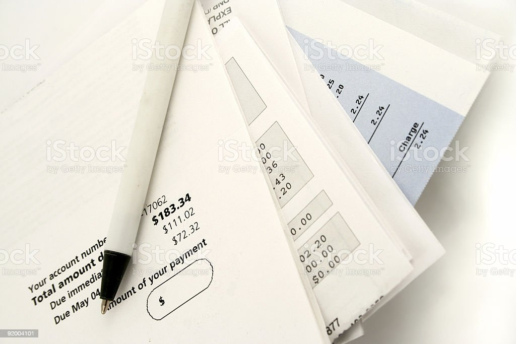 A stacked pile of bills and a white pen stock photo