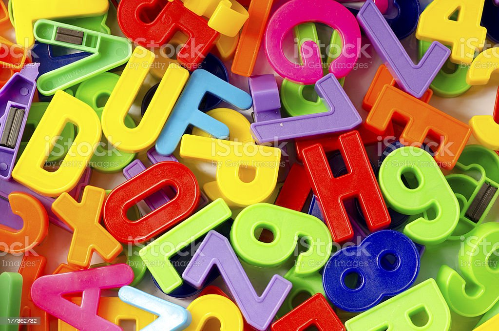 A stacked pile of colored letters and numbers stock photo