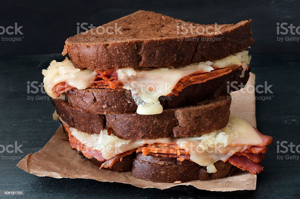 Stacked Reuben Sandwiches against a dark slate background stock photo