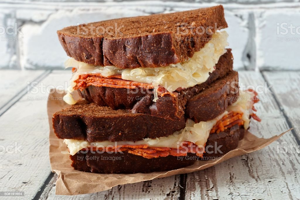 Stacked Reuben Sandwiches against white wood stock photo