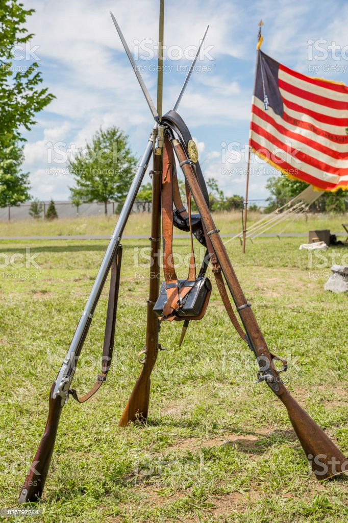 Stacked Rifles Belonging To American Civil War Soldiers, With Old American Flag In Background stock photo