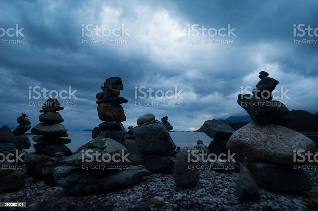 Stacked rock cairns on pebble beach stock photo
