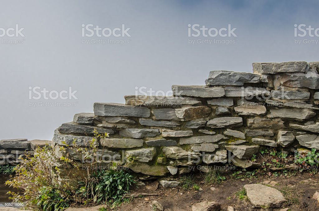 Stacked Stone Wall with Cloudy Background stock photo