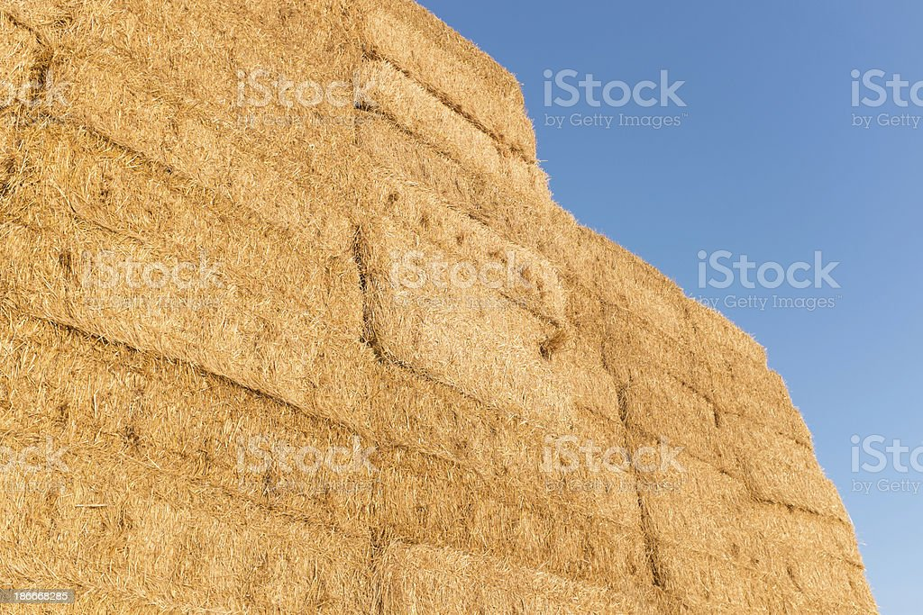 Stacked straw bales against blue sky stock photo