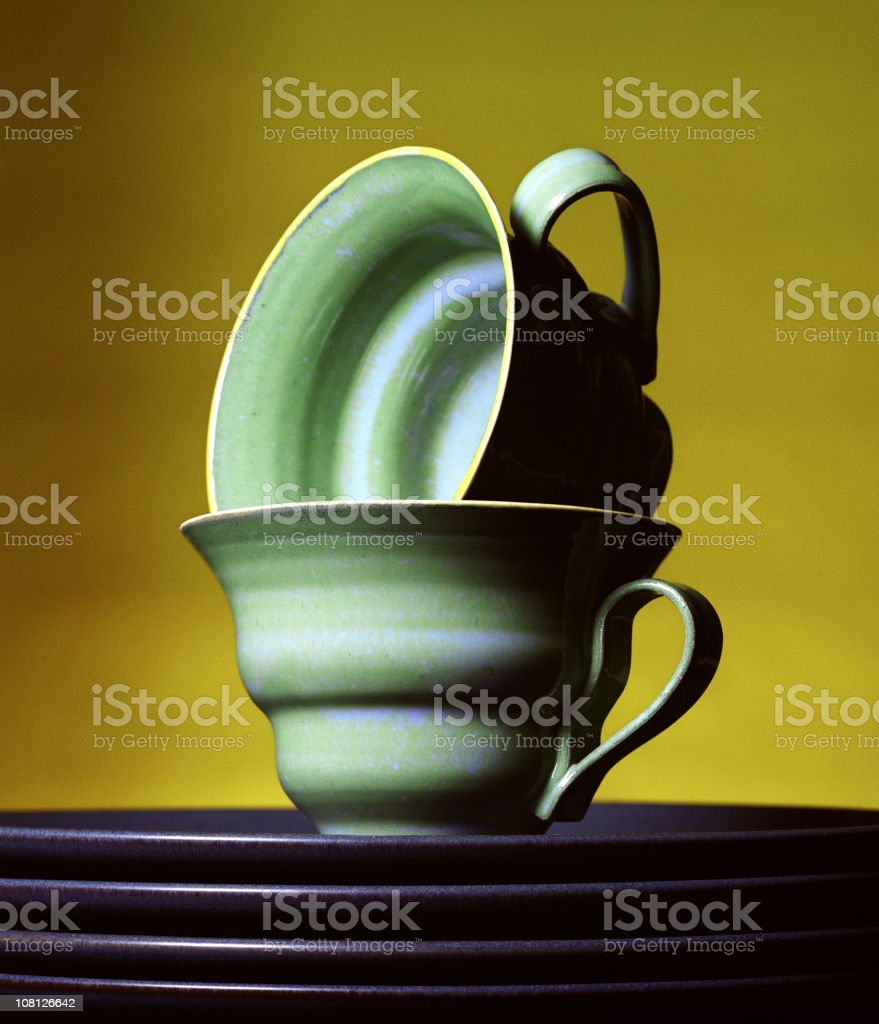 Stacked Teacups and Plates on Yellow Background royalty-free stock photo