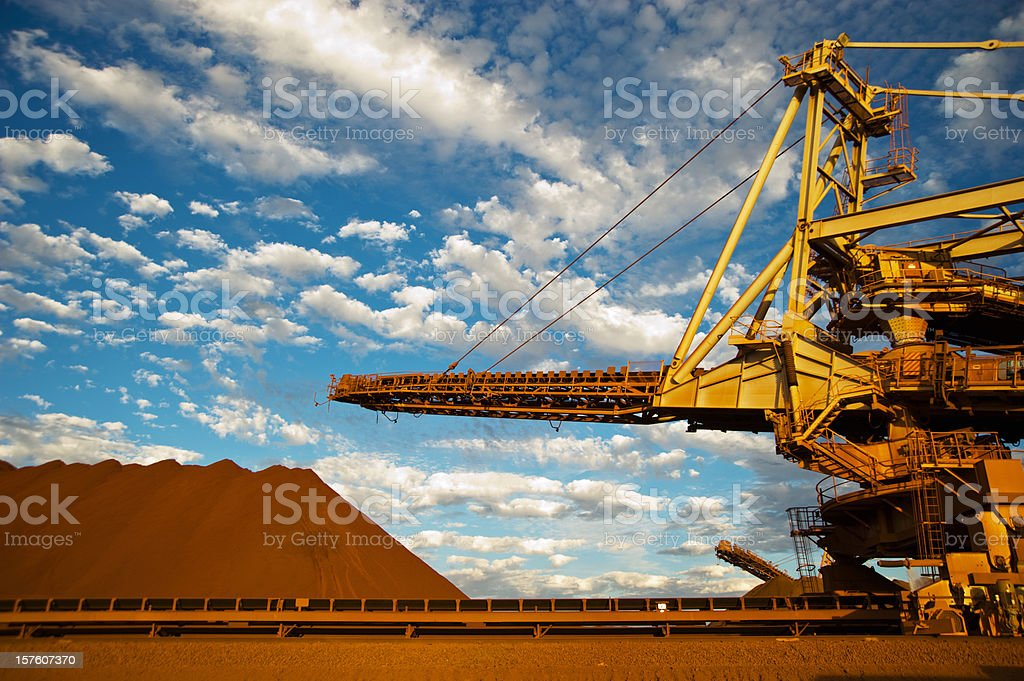 A stacker and stockpile on an iron ore mining site stock photo