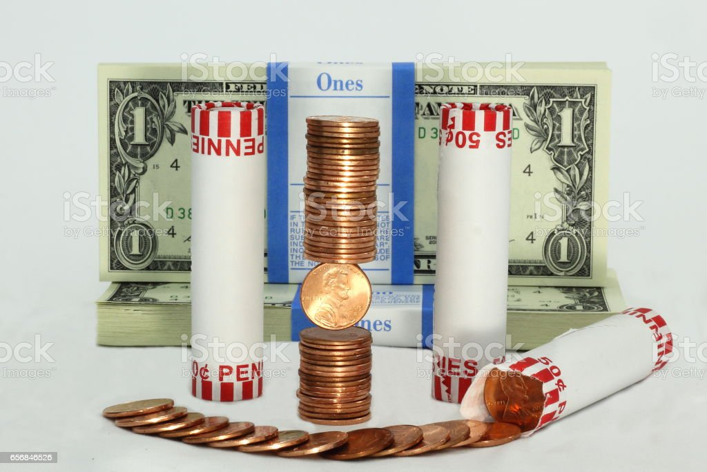Stacks and Rolled Pennies in Front of US Dollars stock photo
