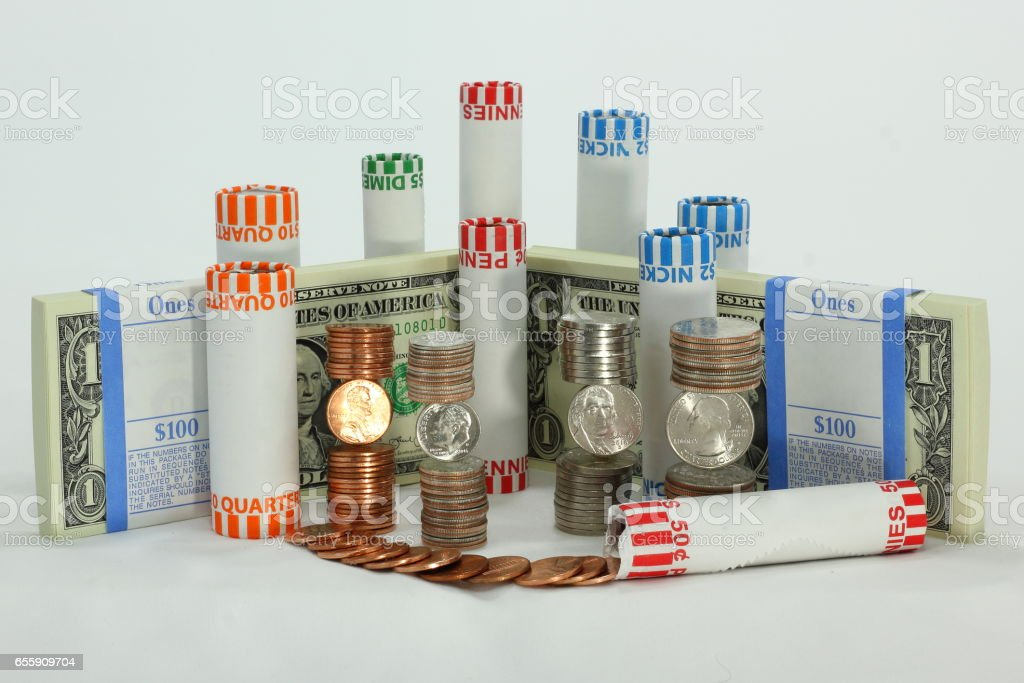 Stacks and rolls of Coins Surrounding Bundles of U.S. Dollars stock photo