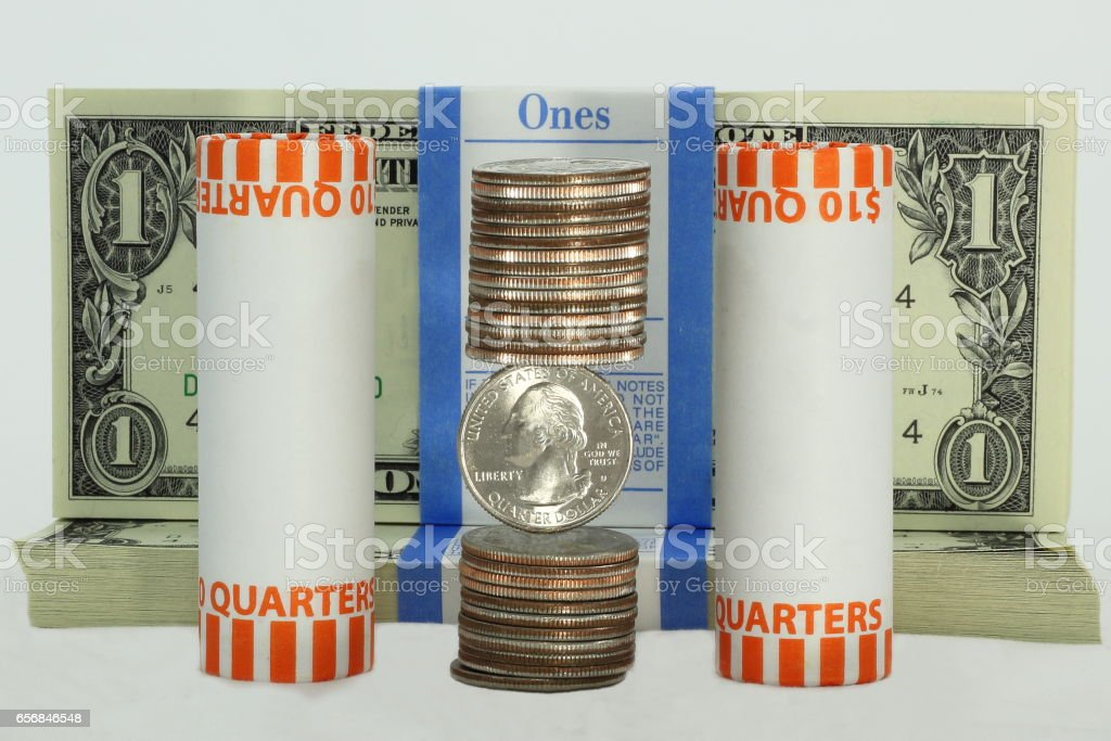 Stacks and Rolls of Quarters in Front of US Dollars stock photo