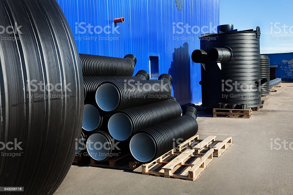 stacks of black pvc plastic pipe outdoors with fitting stock photo