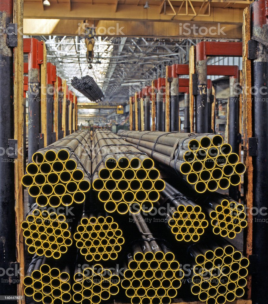 Stacks of bound yellow pipes in an industrial warehouse stock photo