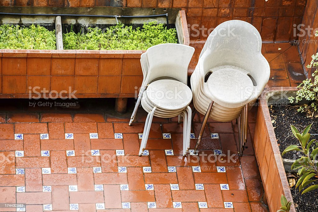 Stacks of Chairs on Patio in Rain stock photo