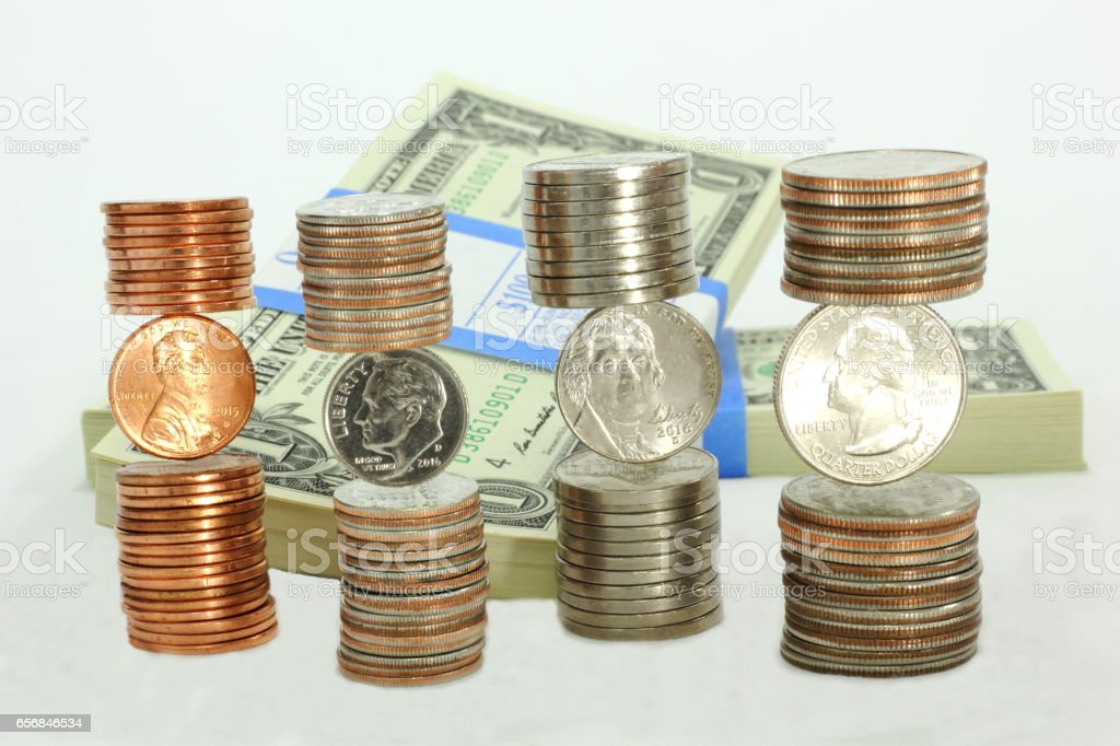 Stacks of Coins and Rolled Coins in Front of Dollar Bundles stock photo