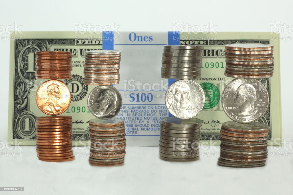 Stacks of Coins in Front of Dollar Bundles stock photo