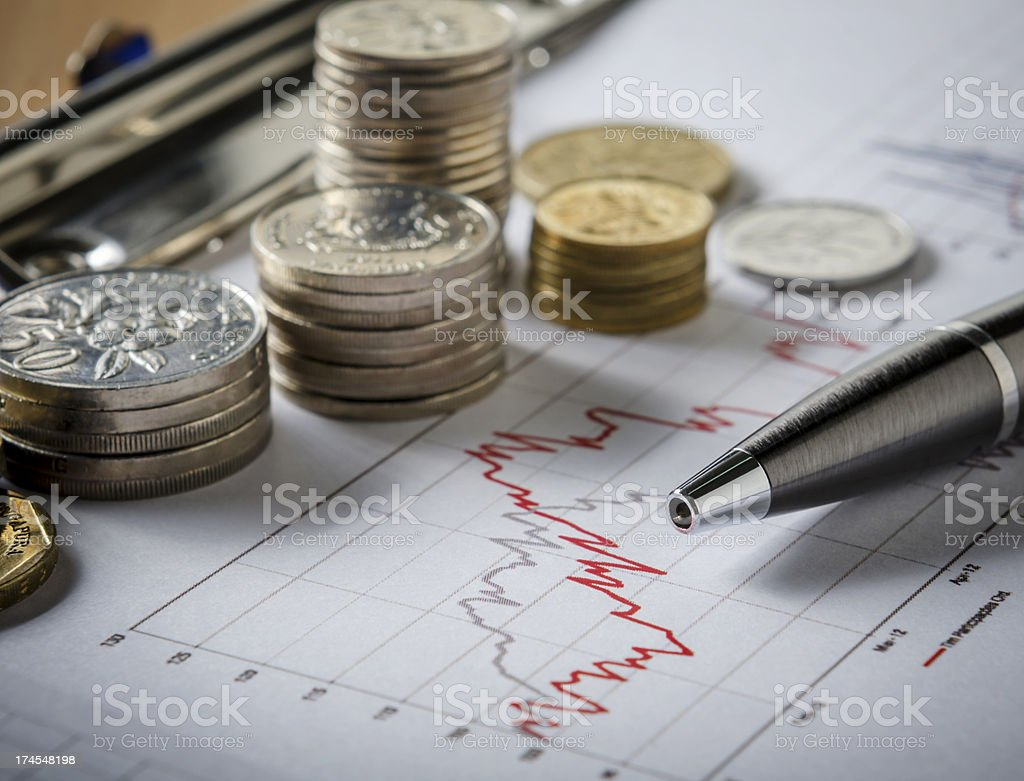 Stacks of coins next to graphs showing results stock photo