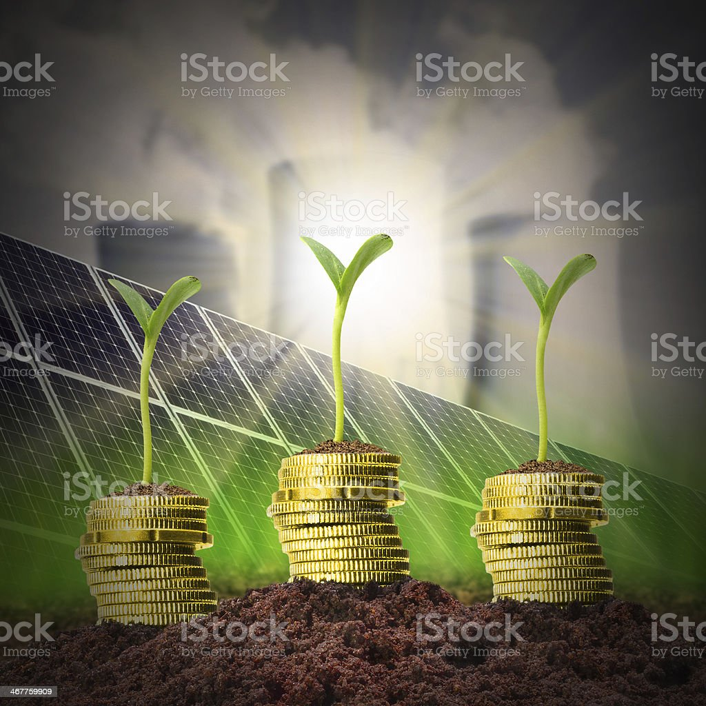Stacks of coins with seedlings and energy sources stock photo