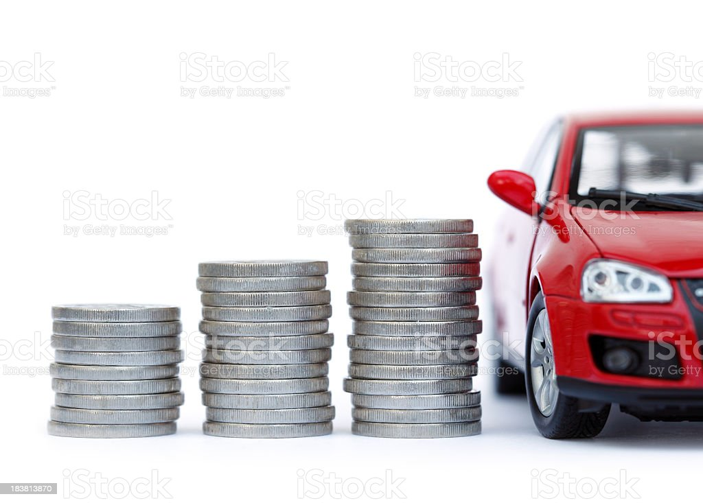 Stacks of giant silver coins next to a new red car stock photo