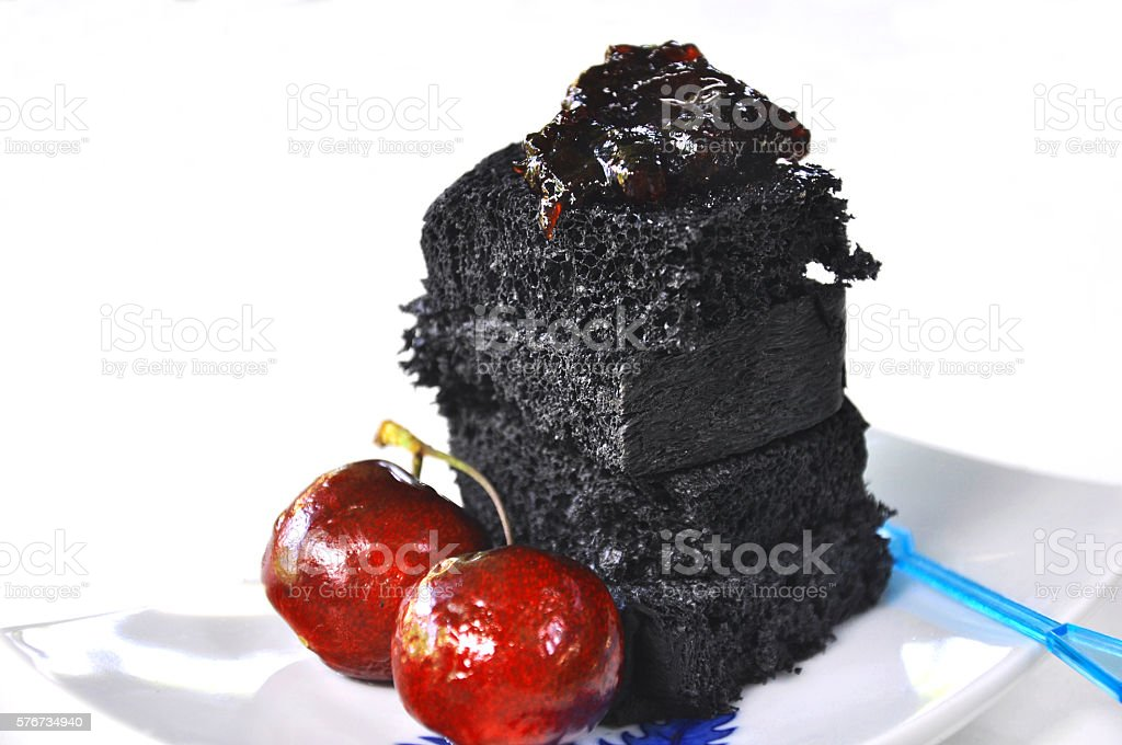 Stacks of organic black charcoal bread with fresh cherry stock photo