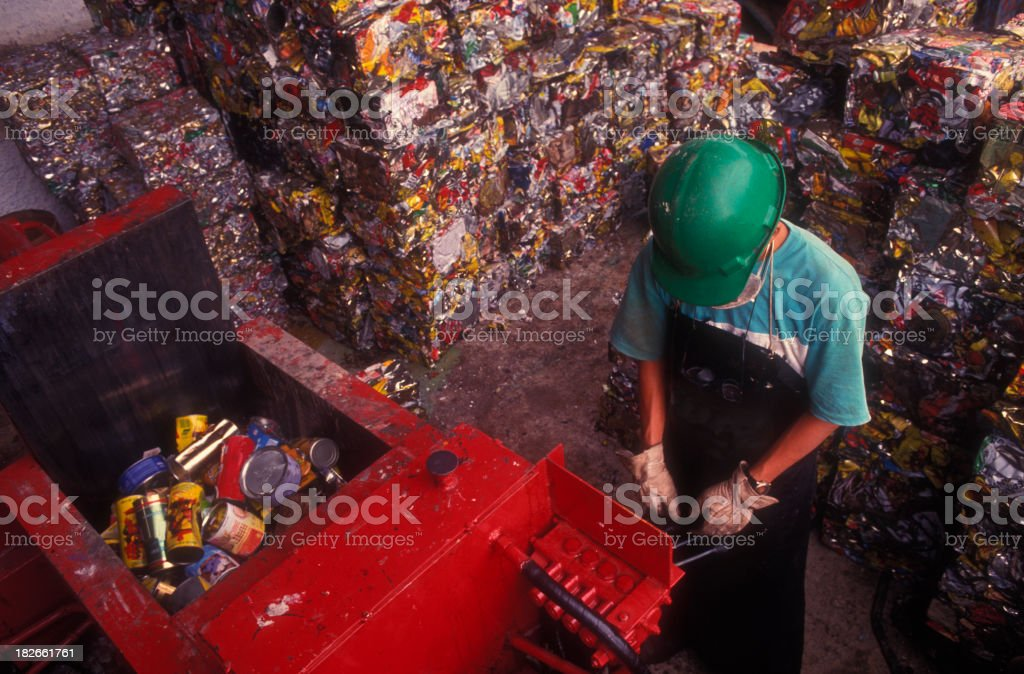 Stacks of recycled cans and a man hard at work royalty-free stock photo