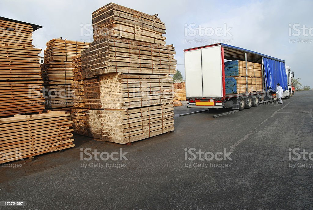 Stacks of timber and loaded truck royalty-free stock photo
