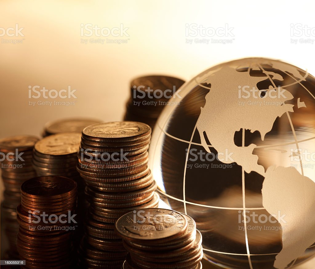 Stacks of U.S. coins next to globe showing North America royalty-free stock photo