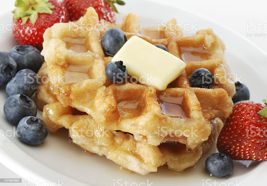 Stacks of waffles surrounded with berries, syrup and butter stock photo